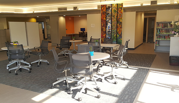 Open office area with tables, chairs, windows