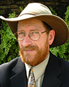 David Michener. White man with full beard wearing a brown hat, suit and tie.